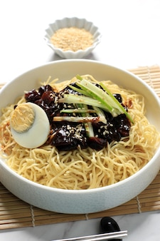 Jajangmyeon or jjajangmyeon  is korean noddle with black sauce, vertical picture with copy space at the top, close up