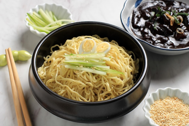 Чачангмён или корейский соус из черной фасоли jajangmyeon, подается с огурцом и кунжутом