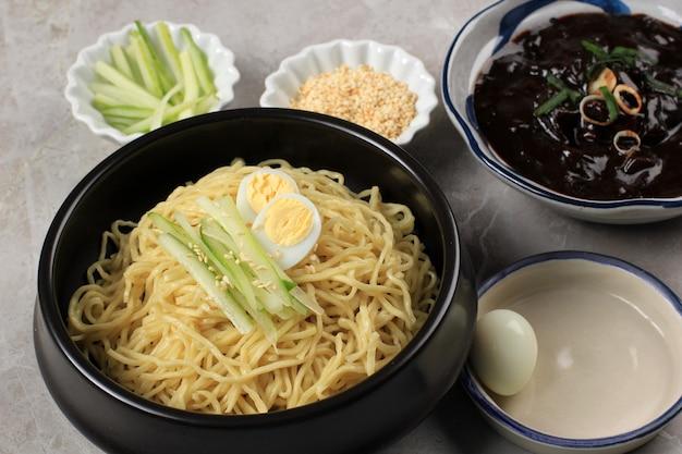 Jajangmyeon или jjajangmyeon korean noddle с соусом из черной фасоли, подается с огурцом и кунжутом