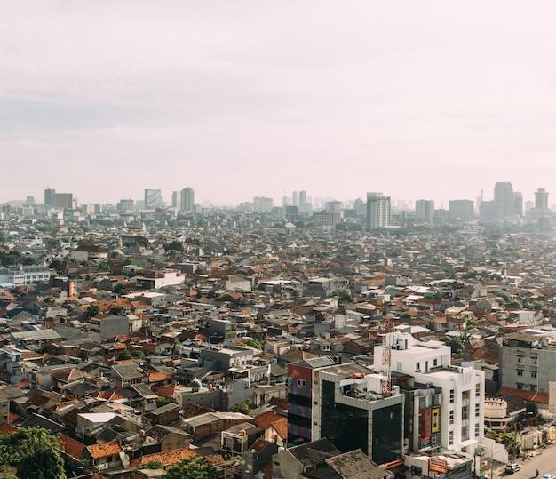 Городской пейзаж джакарты с высотными, небоскребами и красной черепичной крышей местной постройки.