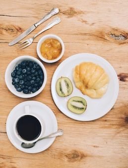 Jam; blueberries; kiwi; bread and coffee cup on wooden textured backdrop