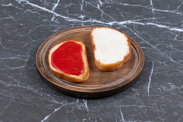 Jam and cheese on two slices of bread on the board , on the marble surface