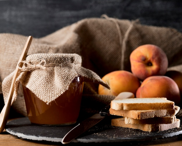 Jam jar with peaches and bread