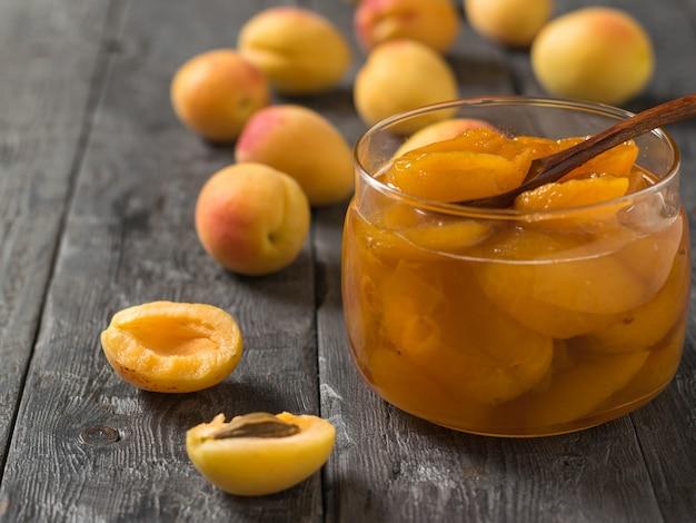 Варенье из спелых абрикосов в стеклянной банке на деревянном столе. свежеприготовленное домашнее варенье.