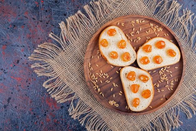 Варенье на нарезанном хлебе на деревянной тарелке, на полотенце, на синем столе.