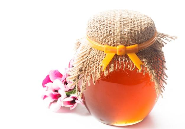 白い背景の上の瓶にジャムまたは蜂蜜