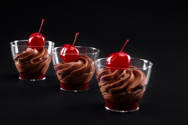 Jam, whipped chocolate cream and cherries served in glasses.
