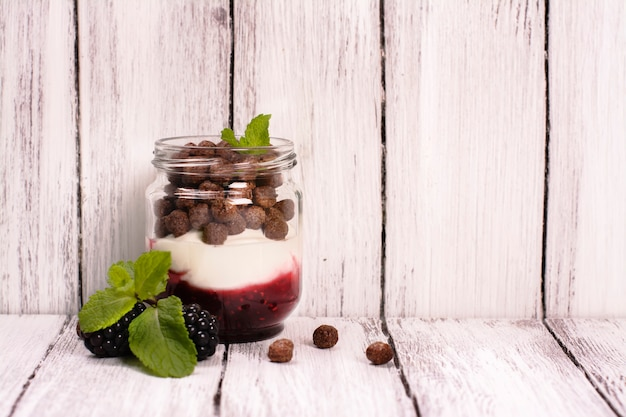 Jam, yoghurt and chocolate balls in glass jars, served with blackberry and mint.