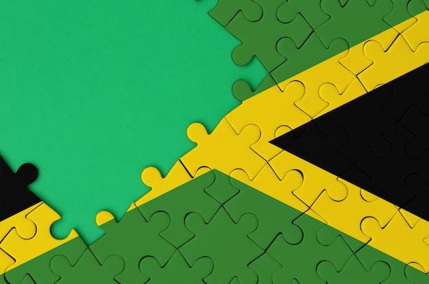 자메이카 국기는 왼쪽에 무료 녹색 복사 공간이있는 완성 된 직소 퍼즐에 그려져 있습니다.
