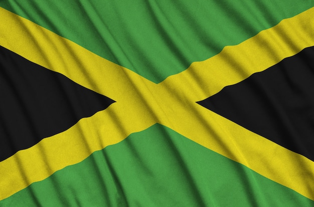 Jamaica flag is depicted on a sports cloth fabric with many folds.