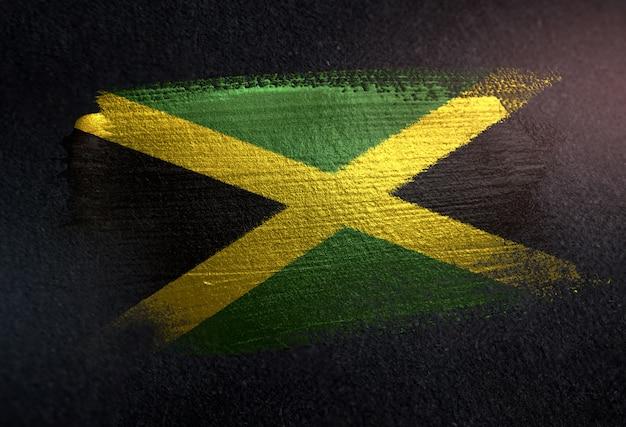 Jamaica flag made of metallic brush paint on grunge dark wall