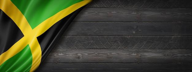 黒い木の壁にジャマイカの旗。水平方向のパノラマバナー。 Premium写真