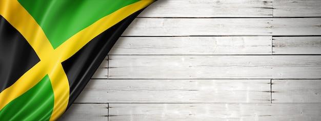 Флаг ямайки на старой белой стене. горизонтальный панорамный баннер.