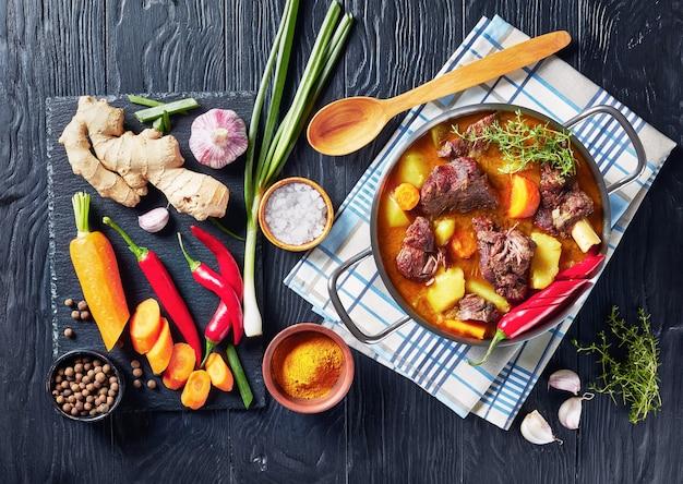 자메이카 카레 염소 천천히 도마에 재료와 함께 검은 나무 테이블에 냄비에 자메이카 매운 염소 카레, 위에서보기, 평면 누워 요리