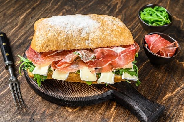 Сэндвич с хамоном и ветчиной на хлебе чиабатта с рукколой и сыром бри камамбер. деревянный стол. вид сверху.