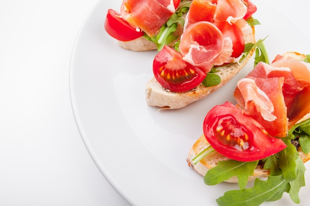 Jamon. slices of bread with spanish serrano ham served as tapas. cured ham, spanish appetizer. prosciutto isolated on white