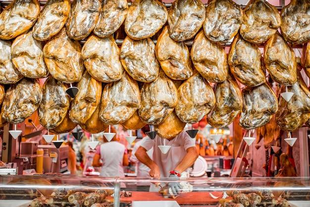 スペイン、バレンシアのマーケットストアにぶら下がっている伝統的なスペインの豚足のハモン