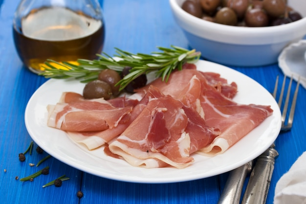 Jamon with olives on white plate