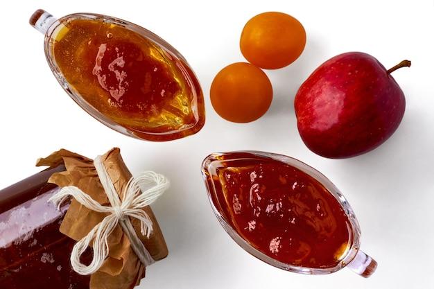 재료로 둘러싸인 흰색 배경에 체리 매실과 사과 잼. 제품 조달. 평면도