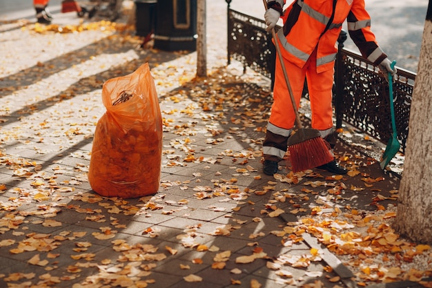 Janitor cleaner sweeping autumn leaves on street