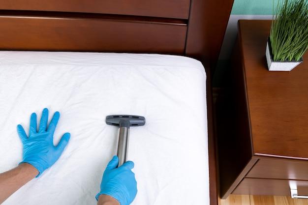 Дворник чистит матрас профессиональным оборудованием в спальне