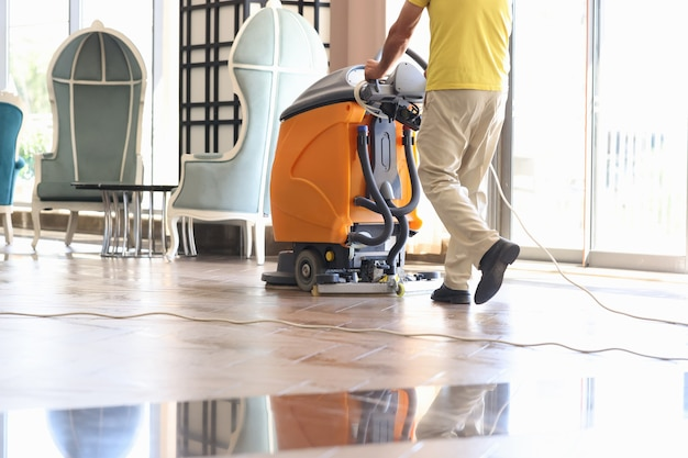 Дворник убирает зал с моющим пылесосом крупным планом