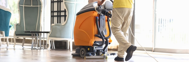 管理人は掃除機のクローズアップを洗ってホールを掃除しています