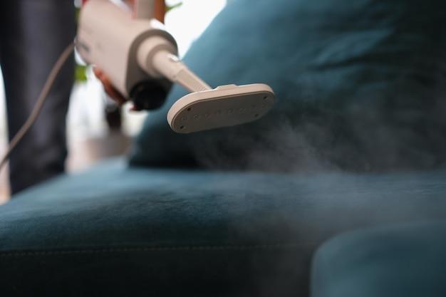 Дворник удаляет грязь с дивана с помощью пароочистителя