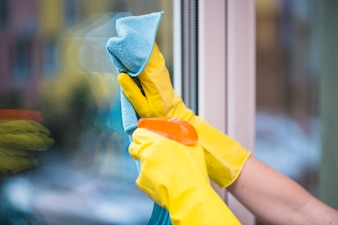 Janitor's hand cleaning glass window with cloth