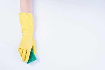 Janitor's hand with yellow gloves holding sponge on white background