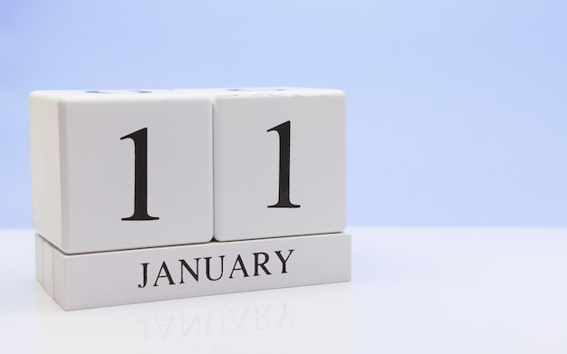 January 11st. day 11 of month, daily calendar on white table with reflection