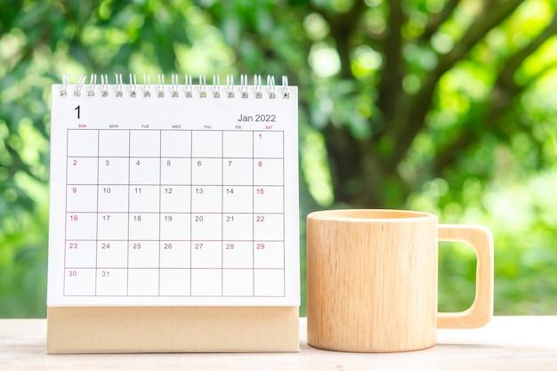 1월 달, 주최자를 위한 캘린더 데스크 2022는 녹색 자연 배경을 가진 나무 테이블에 대한 계획 및 알림을 제공합니다.