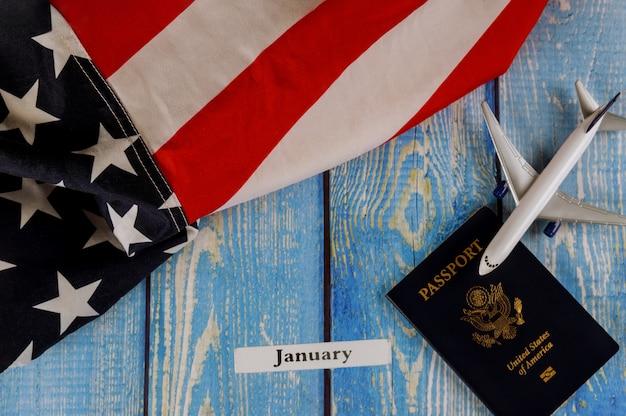 Январь месяц календарного года, путешествия туризм, эмиграция сша американский флаг с паспортом сша и пассажирский макет самолета