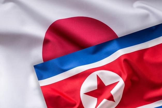 日本と北朝鮮の旗。カラフルな日本と北朝鮮の旗が風になびく。
