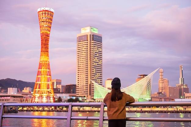 Молодая женщина путешествуя на порте кобе около осака, счастливого азиатского путешественника смотря красивые современные здания на заходе солнца. ориентир и популярный для туристических достопримечательностей в кобе, хиого, japan.asia travel концепция