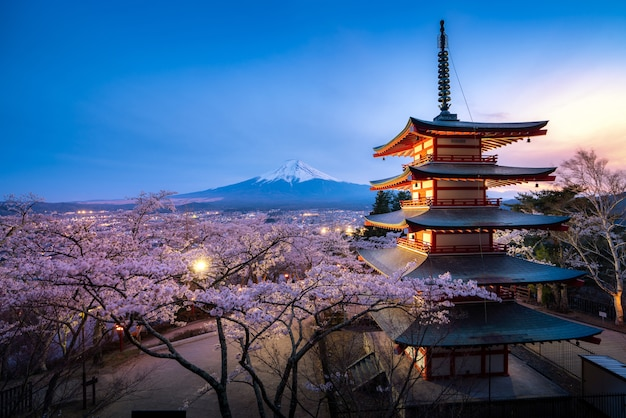 Japan at chureito pagoda and mt. fuji in the spring with cherry blossoms full bloom during twilight.
