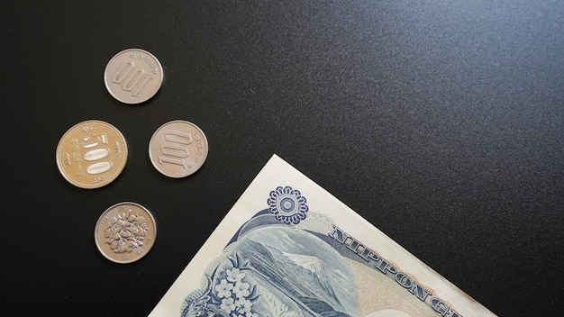 Japan currency paper banknote and coins on dark