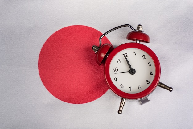 日本の旗とビンテージの目覚まし時計をクローズアップ。日本に旅行する時間。