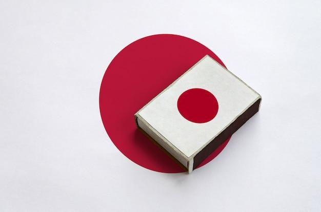 Флаг японии изображен на спичечной коробке, которая лежит на большом флаге