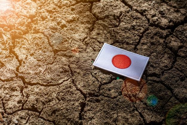 Флаг японии на заброшенной потрескавшейся земле.