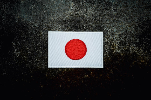 Japan flag on rusty abandoned metal floor in the dark.