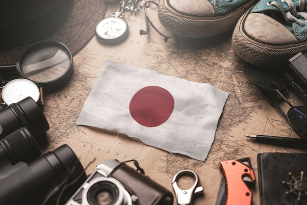 Japan flag between traveler's accessories on old vintage map. tourist destination concept.
