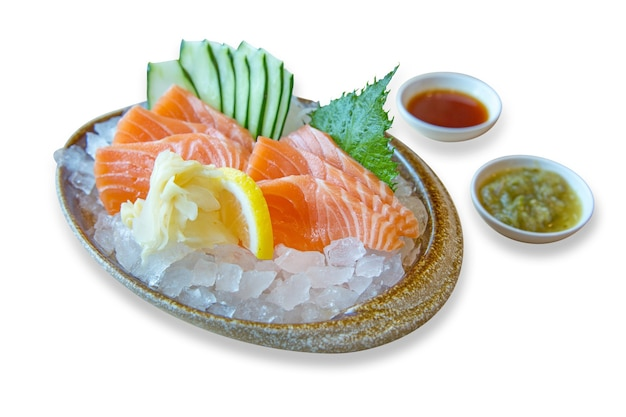 Еда японии, свежий лосось в миске на льду с соусом из морепродуктов и ломтиком огурца, фокус селективный.