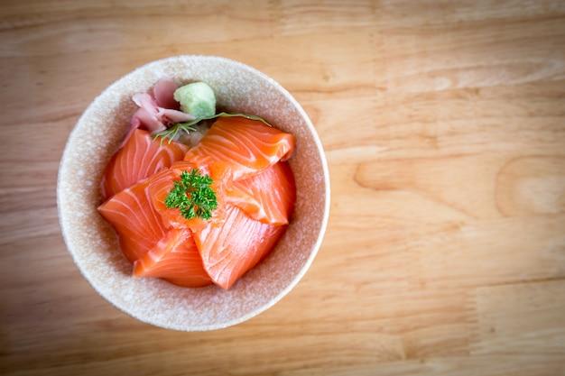 日本食サーモンドン日本米の上にスライスしたサーモンで構成されています木製のテーブルの上の白いボウルにわさびと生姜のピクルスを添えて。