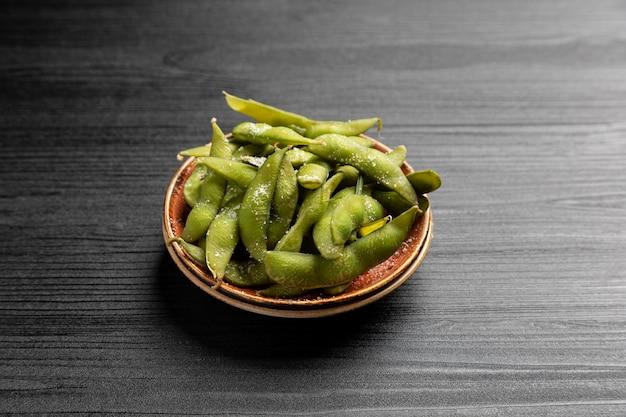 日本の前菜の枝豆、暗い表面に大豆のさや。