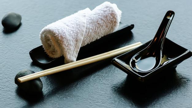 Japanese, asian food utensils - pair of chopsticks, hot weat towel, ceramic black spoon, dark stone in restaurant, cafe