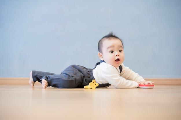 방에 나무 바닥에 기어가는 일본 아기