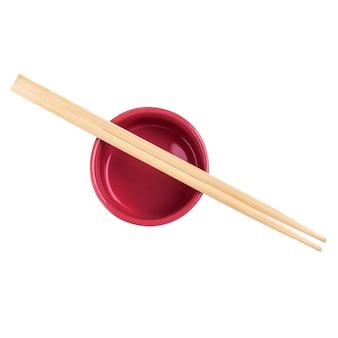 白い背景で隔離の赤いソースボウルの上の日本の竹寿司スティックまたは箸