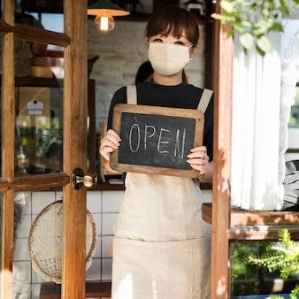 カフェでフェイスマスクの日本のバリスタ女性