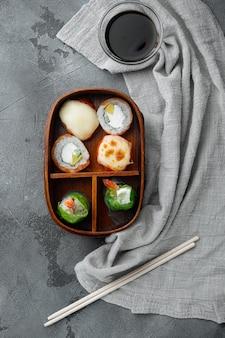 Японский ланч-бокс бенто с набором палочек для еды, на сером камне